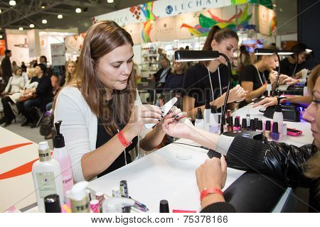 MOSCOW - OCTOBER 24: Manicurist a manicure at the international exhibition of professional cosmetics and beauty salon equipment INTERCHARM on October 24, 2014 in Moscow