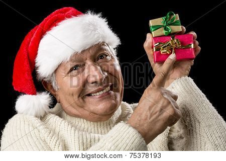 Smiling Senior Pointing At Two Wrapped Xmas Gifts
