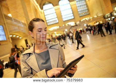 Businesswoman in grand central station looking at departure times