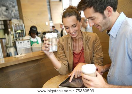 Couple websurfing on tablet in coffee shop