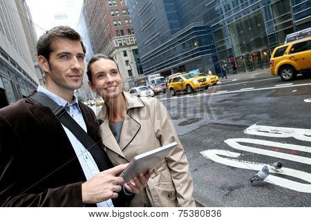 Business people using tablet in the street of Manhattan