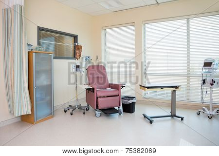 Empty chair with IV drip stand and table in chemo room