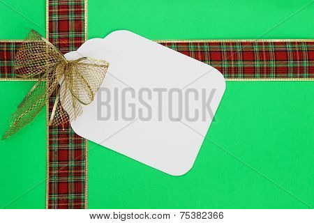 Big Christmas gift tag with red and gold ribbon on green wrapping paper background