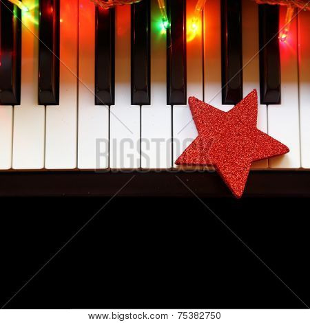 Christmas lights and ornament on piano keys