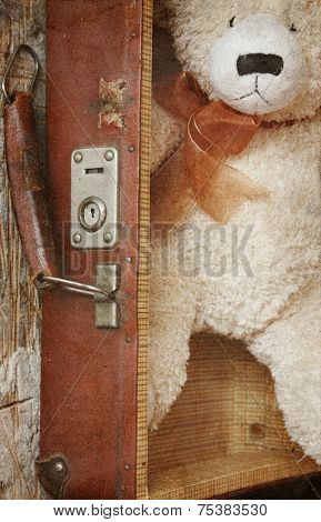 Vintage-style teddy bear and old suitcase