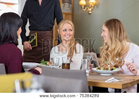 Happy young women having meal together at coffeeshop while waiter standing with menu