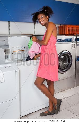 Side view portrait of young woman putting clothes in washing machine at laundry