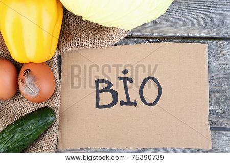 Eggs and vegetables with inscription BIO on card, on wooden background. Organic food concept
