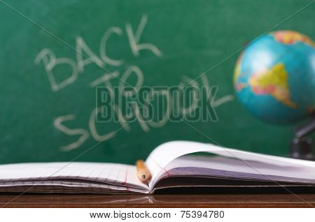 Open notebook with pencil with globe and Back to school handwritten on the chalkboard