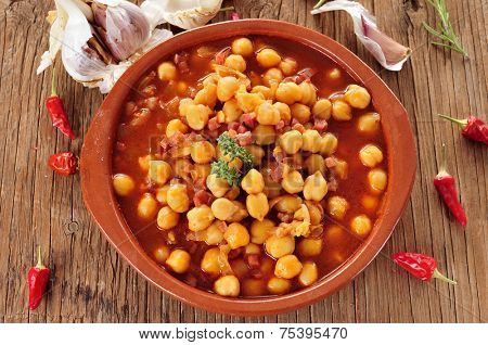 an earthenware bowl with potaje de garbanzos con jamon, a spanish chickpeas stew with ham, on a rustic wooden table