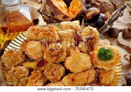 closeup of a plate with panellets, and some roasted chestnuts and sweet potatoes, and sweet wine, typical snack in All Saints Day in Catalonia, Spain