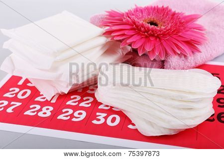 Sanitary pads, calendar, towel and pink flower on light background