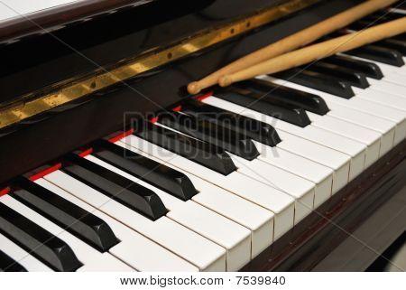 Diagonal Shot Of Drum Sticks On Piano Keyboard