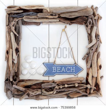 Driftwood frame and beach sign with cockle shells over wooden white background.