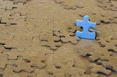 image of child missing  - Cropped blue puzzle iece on brown background - JPG