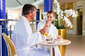 stock photo of thermal  - Woman and man eating snack with coffee and cake in thermal spa - JPG