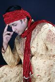 stock photo of sherwani  - A royal Indian man in a traditional attire lost in his thoughts - JPG