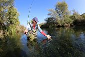 pic of fly rod  - Fly fisherman catching a fario trout in river - JPG