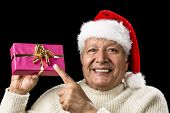 Постер, плакат: Joyous Old Man Pointing At Magenta Wrapped Gift