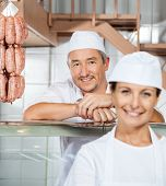 stock photo of slaughterhouse  - Portrait of happy mature male butcher with female colleague at butchery - JPG