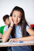 stock photo of schoolgirl  - Portrait of happy teenage schoolgirl sitting at desk in classroom - JPG