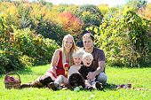 stock photo of orchard  - a happy family of four attractive caucasian people is sitting in an apple orchard in the Autumn forest eating a fresh fruit picnic - JPG