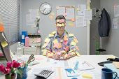 image of sticks  - Office worker sitting at desk covered with colorful post it stick notes - JPG