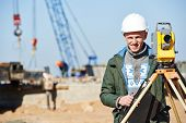 stock photo of theodolite  - Surveyor builder worker with theodolite transit equipment at construction site outdoors during surveying work - JPG