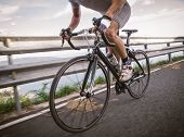 stock photo of pedal  - Detail of a road bike with a cyclist pedaling on a road - JPG