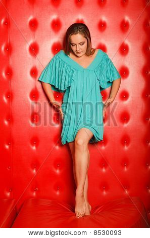 woman in a turquoise dress stands on a red leather couch