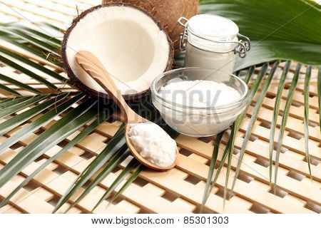 Coconut with leaf and coconut oil in jar on wooden background
