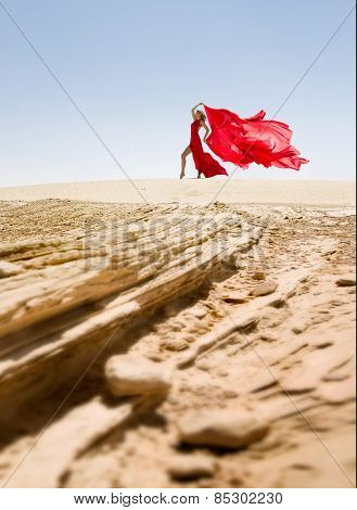 Beautiful and sexy slim woman, red dress in desert
