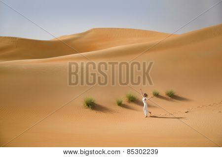 Beautiful sand dunes, grass and a slim running woman in white dress