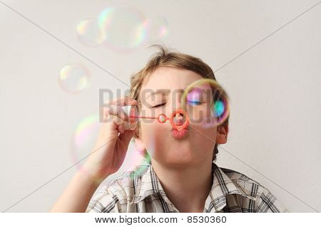 Little Caucasian Boy Blowing Soap Bubbles On White Background, Front View