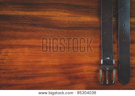 Mans leather belt on wooden table