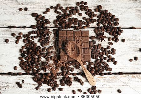Still life with chocolate, grains and spice on wooden background