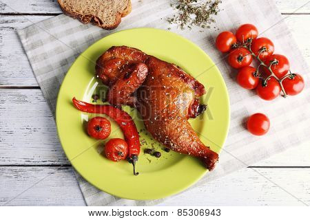 Smoked chicken leg  with vegetables on plate on table close up