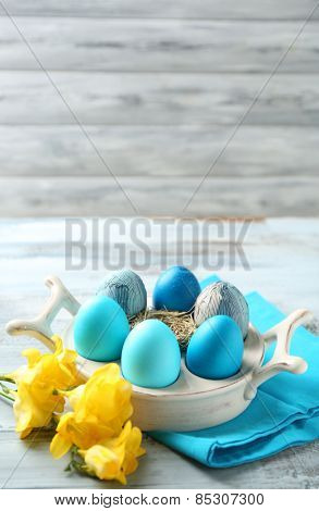 Easter composition with colorful eggs on holder on wooden table background