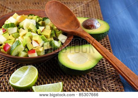 Salad with apple and avocado in bowl on wicker stand close up