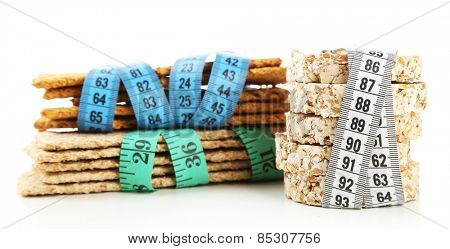 Fresh crispbread with measuring tapes, isolated on white - diet concept