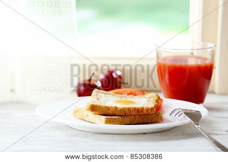 Scrambled egg with bread on plate with glass of juice on bright background