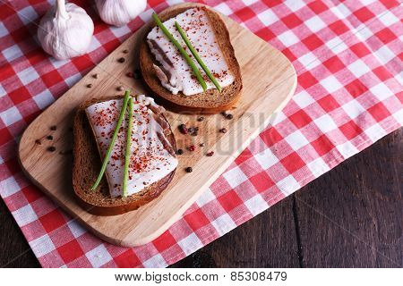Sandwiches with lard on cutting board and garlic on table close up