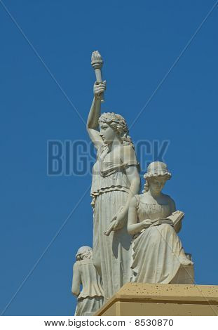 The Three Muses Marble Statues against a Blue Sky