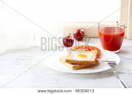 Scrambled egg with bread on plate with glass of juice on light background