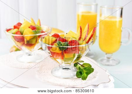 Fruit salad with mint and orange juice in glassware on wooden table and planks background