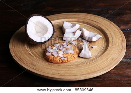 Cookie with cracked coconut on cutting board and rustic wooden table background