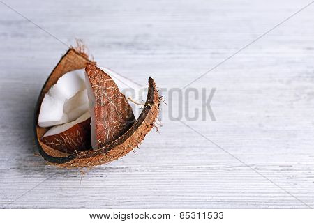 Cracked coconut on color wooden table background