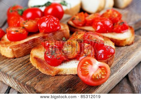 Slices of white toasted bread with canned tomatoes on cutting board on wooden table, closeup