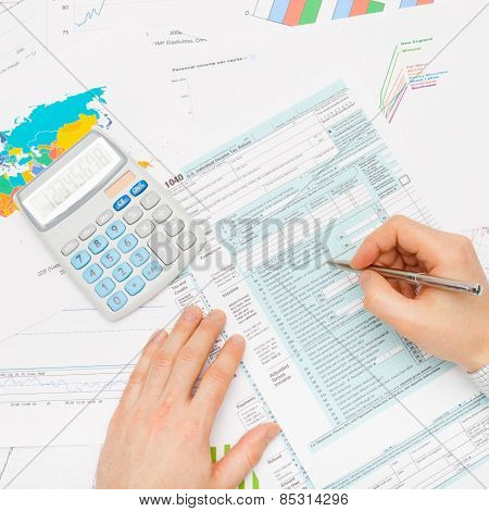 Male Filling Out 1040 Us Tax Form With Silver Pen