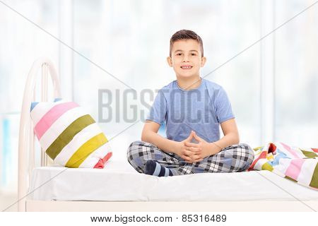 Cute little boy in pajamas sitting on a bed at home